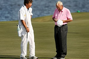 A caddie gets his hat signed by Arnold Palmer after the Devon Quigley Pro-Am at the Floridian on the 18th green.