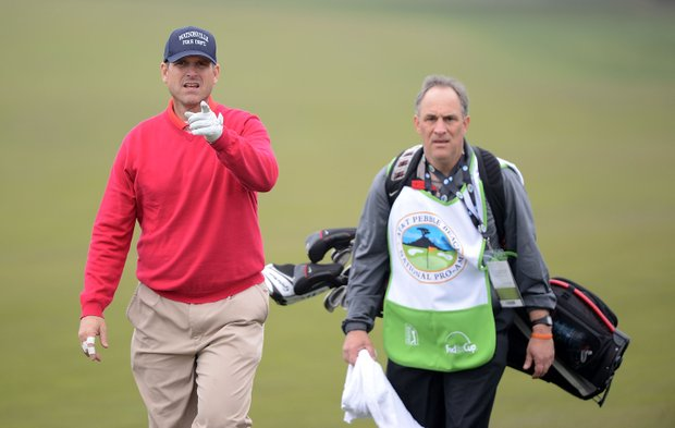 San Francisco 49ers head coach Jim Harbaugh walks with his caddie during the first round of the AT&T Pebble Beach National Pro-Am at the Monterey Peninsula Country Club.
