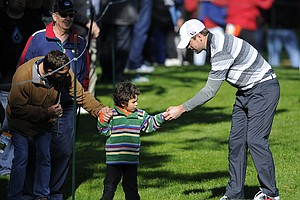 Green Bay Packers quarterback Aaron Rodgers gives a golf ball to a young fan on the 8th hole during the second round of the AT&T Pebble Beach National Pro-Am at Spyglass Hill.