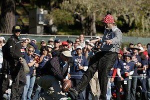 Actor Bill Murray kicks a football held by former NFL player Harris Barton on the 15th hole during the third round of the AT&T Pebble Beach National Pro-Am at Pebble Beach Golf Links.