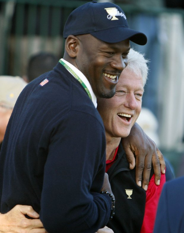 Former U.S. President Bill Clinton jokes with Michael Jordan at The President's Cup in 2009.
