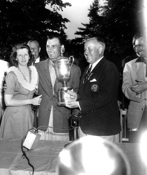 Ben Hogan smiles over a crowd and poses with his wife, Valerie, as he receives the U.S. Open Golf Championship trophy in Ardmore, Pa., on June 11, 1950. Presenting the cup is James D. Standish, Jr., Detroit president of the United States Golf Association.