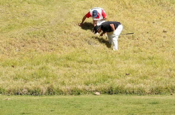 Fredrik Jacobson of Sweden locates his ball in the tall grass on the fifth hole during the third round of the Northern Trust Open.