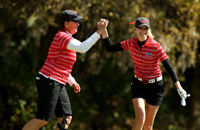 Southern Methodist University head coach Jeanne Sutherland high fives with Jenny Haglund after she chipped in at No. 18 during the Central District tournament at River Wilderness in Parrish.