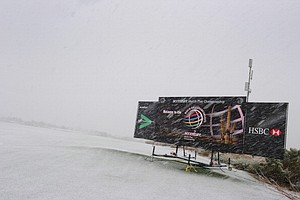 An electronic leaderboard is showered by snow on the practice range as snow and rain caused play to be suspended due to weather during the first round of the World Golf Championships-Accenture Match Play Championship at The Golf Club at Dove Mountain.