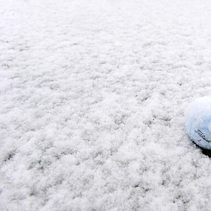 Snow continues to fall on a golf ball on the practice range. Play to be suspended due to weather at the World Golf Championships-Accenture Match Play Championship.