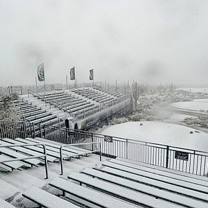 Snow covers the first tee and the grandstands as play was suspended during the first round of the World Golf Championships - Accenture Match Play at the Golf Club at Dove Mountain in Marana, Ariz.