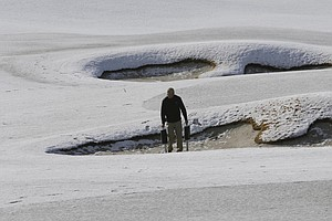 A groundskeeper picks up practice balls out of bunkers on the practice range before play resumes for the first round of the WGC-Accenture Match Play Championship, Thursday, Feb. 21, 2013, in Marana, Ariz.
