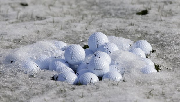 Practice balls sit in frozen slush on the practice range before play resumes for the first round of the WGC-Accenture Match Play Championship, Thursday, Feb. 21, 2013, in Marana, Ariz.