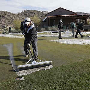 A groundskeeper rolls melted snow off the putting green before play resumes for the first round of the WGC-Accenture Match Play Championship, Thursday, Feb. 21, 2013, in Marana, Ariz.