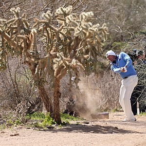 Matt Kuchar hits a shot from behind a tree on the ninth hole during the final round of the WGC-Accenture Match Play Championship.