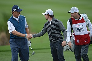 World No. 1 and defending champion, Rory McIlroy shakes hands with Open champion Ernie Els as he walks off the course on the 18th hole.