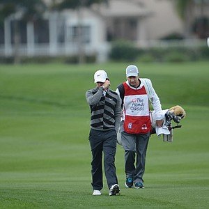 World No. 1 and defending champion, Rory McIlroy walks off the course on the 18th hole with caddie J.P Fitzgerald.
