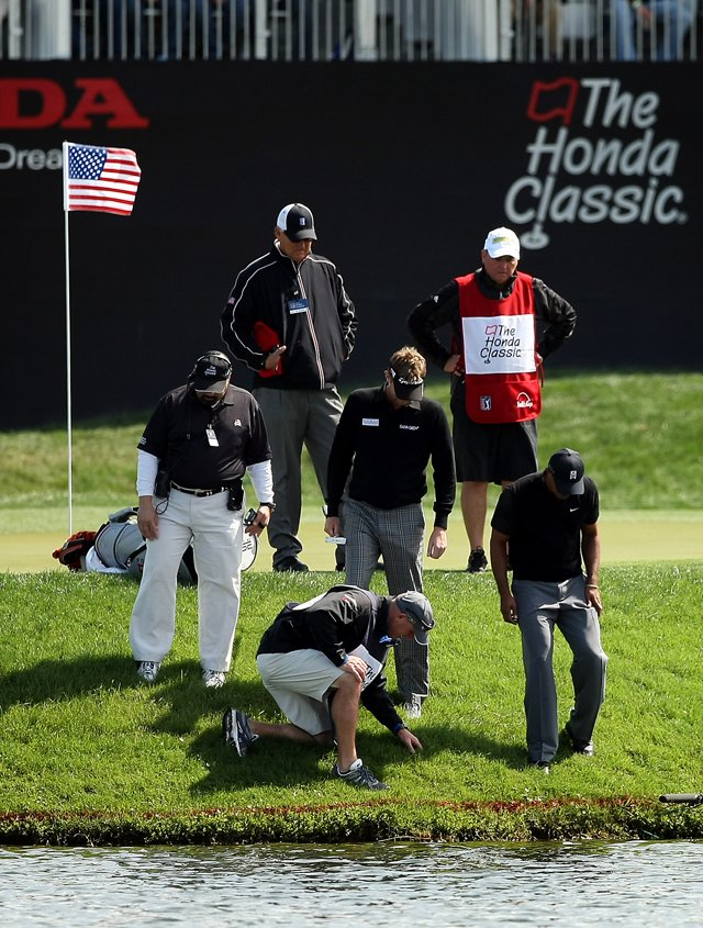 Tiger Woods, bottom right, along with playing partner David Lynn and their caddies try to search for Woods&#39; ball at No. 17 during the Honda Classic on Saturday.