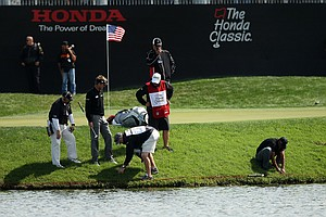 Tiger Woods, crouched far right, digs for his ball at No. 17 during the Honda Classic on Saturday.