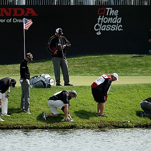 A rules official looks at his watch as Tiger Woods, kneeling far right, searches for his ball at No. 17 along with his playing partner David Lynn and their caddies during the Honda Classic on Saturday.