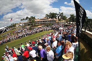 Fans watch as Tiger Woods hits his tee shot on the first hole during the final round of the WGC-Cadillac Championship.