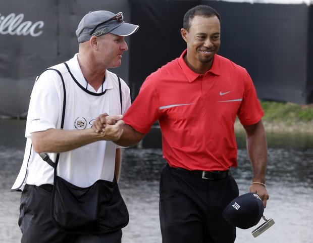 Tiger Woods and caddie Joe Lacava celebrate Sunday's win at the WGC-Cadillac Championship in Doral, Fla.