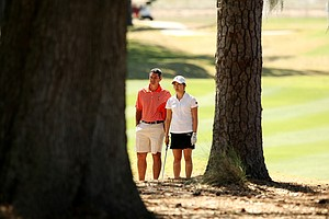 Oklahoma State's Alan Bratton with his player Julie Yang among the trees at No. 9.