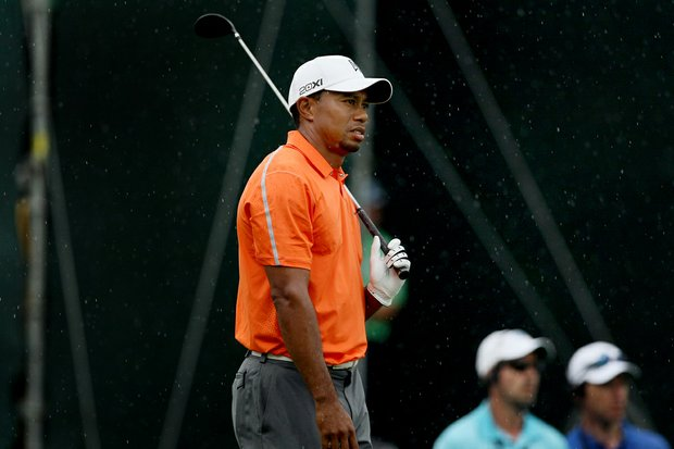 As the rain comes down Tiger Woods watches his shot at No. 18 in Round 2 of the Arnold Palmer Invitational.