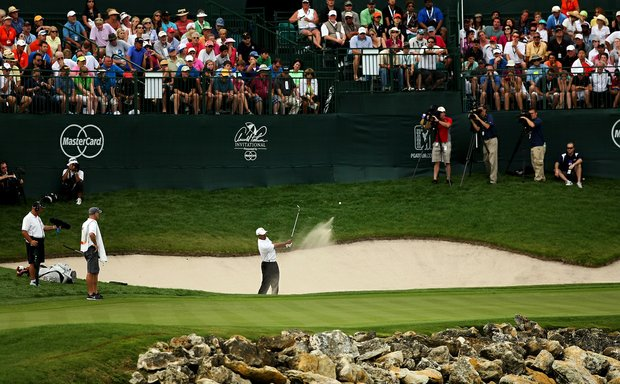 Tiger Woods hits out of the bunker at No. 18 on Saturday at Arnold Palmer Invitational. He has the lead by two shots over Rickie Fowler.