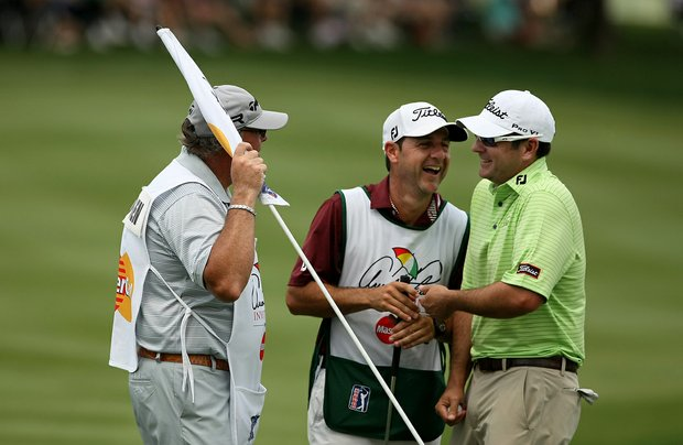 Ben Curtis shares a laugh with two caddies after he narrowly made a putt at Bay Hill's eighth.