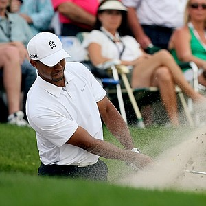 Tiger Woods hits out of a greenside bunker at No. 8 on Saturday.