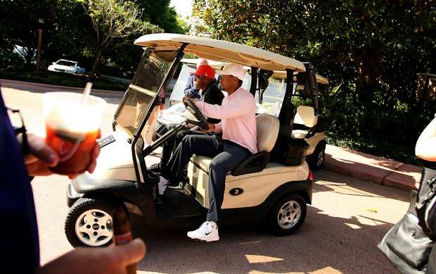 Tiger Woods hops into a golf cart to head to the range during the 2013 Tavistock Cup at Isleworth Country Club.