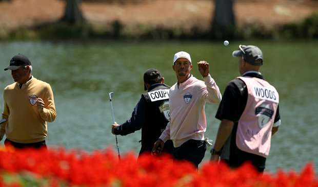 Joe LaCava tosses the ball to Tiger Woods during the 2013 Tavistock Cup at Isleworth Country Club.