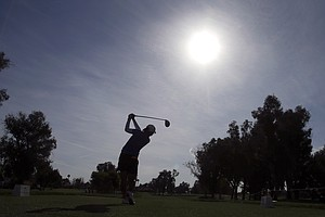 Lydia Ko, of New Zealand, is silhouetted as she hits from the tee on the 12th hole during the first round of the LPGA Kraft Nabisco Championship.
