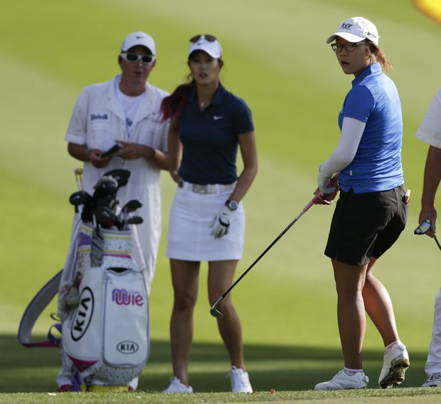 Lydia Ko, of New Zealand, right, and Michelle Wie wait to hit on the 11th hole during the first round of the LPGA Kraft Nabisco Championship.