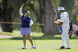 Lizette Salas, left, throws pieces of grass into the air to test the wind on the ninth hole during the third round of the Kraft Nabisco Championship