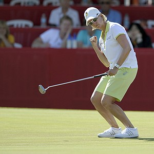Karrie Webb, of Australia, pumps her fist as she anticipates a birdie putt falling into the cup on the 18th hole during the third round of the Kraft Nabisco Championship.