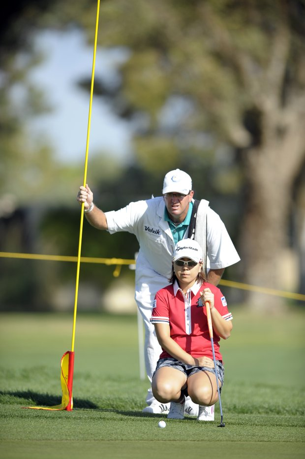 Mika Miyazato, of Japan, reads the green with her caddie Chad Payne on the third hole during the third round of the LPGA Kraft Nabisco Championship.