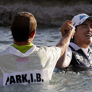 Inbee Park, right, of South Korea, celebrates after jumping into Poppy's Pond with caddie Brad Beecher after winning the LPGA Kraft Nabisco Championship.