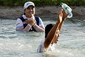 Inbee Park, left, of South Korea, celebrates after jumping into Poppy's Pond after winning the LPGA Kraft Nabisco Championship.