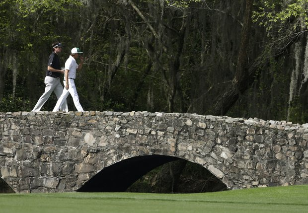 Bubba Watson, left, walks across the Nelson Bridge to the 13th hole with Rickie Fowler during a practice round for the Masters in Augusta, Ga.