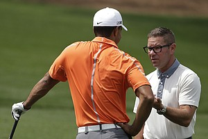 Tiger Woods, left, listens to his coach Sean Foley on the driving range at the Masters.