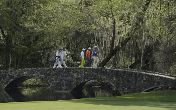 Tiger Woods, center, walks over the Nelson Bridge with amateur Guan Tianlang, of China, and Dustin Johnson, right, during a practice round for the Masters.