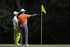 Tiger Woods, right, gives direction to amateur Guan Tianlang, of China, on the 11th green at Augusta National.