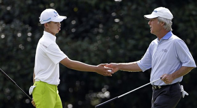 Ben Crenshaw, right, hands a golf ball to amateur Tianlang Guan, of China, on the 11th hole during a practice round for the Masters.