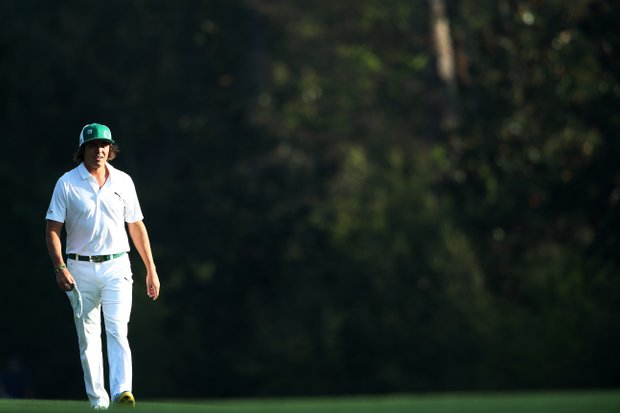Rickie Fowler walks along a fairway during a practice round prior to the start of the 2013 Masters.