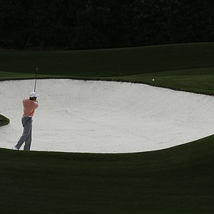 Tiger Woods chips out of a bunker on the fourth hole during a practice round for the Masters on Tuesday.