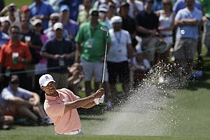 Tiger Woods watches his shot out of a bunker on the second hole during a practice round for the Masters.