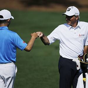 Fred Couples bumps fists with amateur Tianlang Guan during a practice round Tuesday for the 2013 Masters at Augusta National.