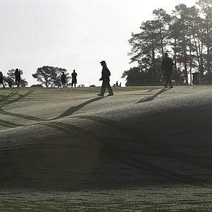 Spectators walk across a dew covered first fairway before Tuesday's practice round for the 2013 Masters at Augusta National.