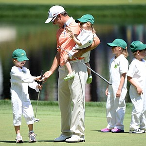 Trevor Immelman of South Africa plays with his kids during the Par-3 Contest.