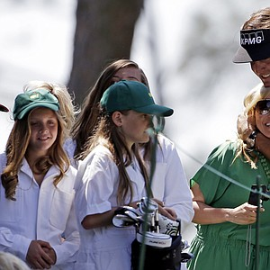Phil Mickelson kisses his wife Amy as his daughters look on after teeing off on the first hole during the Masters Par-3 Contest.