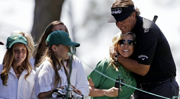 Phil Mickelson kisses his wife Amy as his daughters look on after teeing off on the first hole during the Par 3 Contest before the Masters.