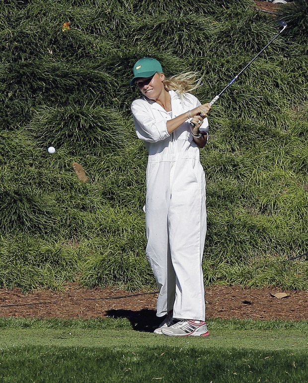 Tennis player Caroline Wozniacki tees off on the ninth hole during the par three competition before the Masters.